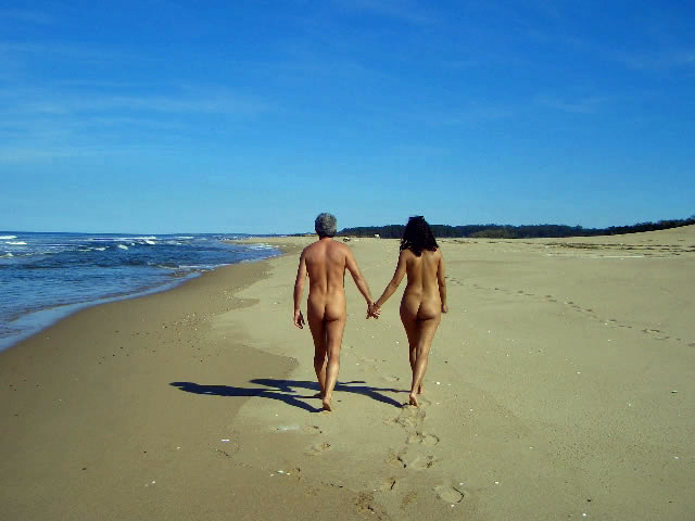 Naked_couple_walking_along_the_beach_(Chihuahua,_Uruguay)